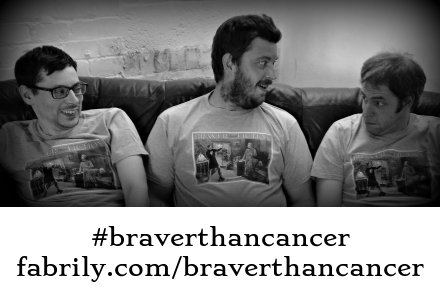 Martin (guitar), Paul (drums) and Adam (bass) on the sofa at rehearsals, wearing their #braverthancancer T-shirts.